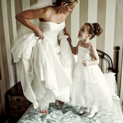 Bride and Flower Girl Jumping on Bed