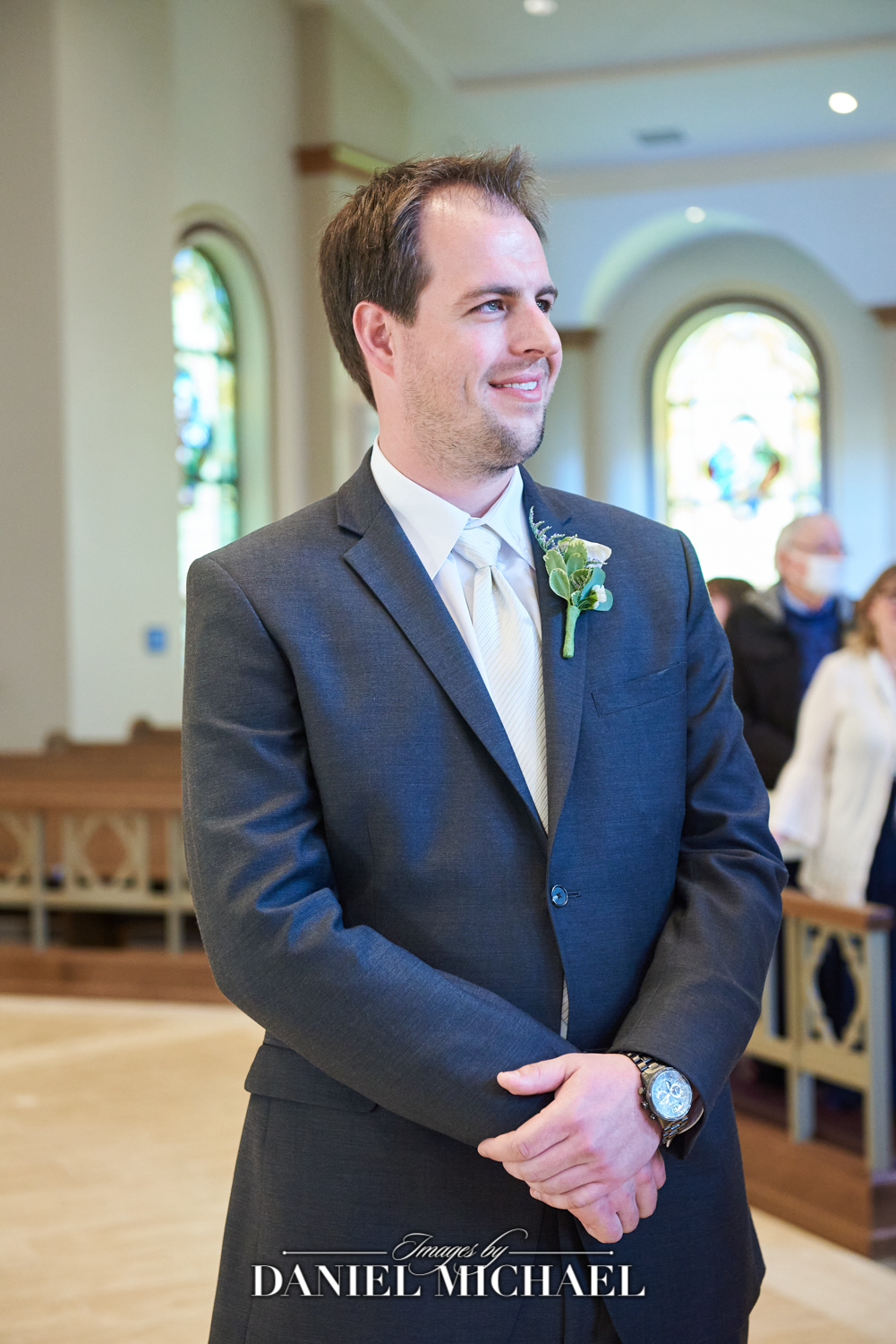 Photographer catching groom's expression as Bride Walks